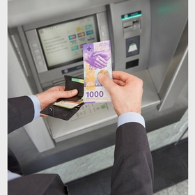 1000-franc notes being withdrawn from an ATM