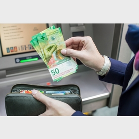 50-franc notes being withdrawn from an ATM